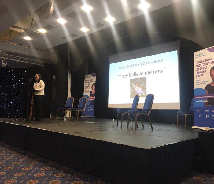 Sarah Henry on stage giving presentation